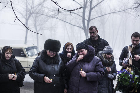 Relatives of a 4-year-old child killed in a Ukrainian Army artillery strike mourn during his funeral on the outskirts of Donetsk in eastern Ukraine on Tuesday, Jan. 20, 2015.