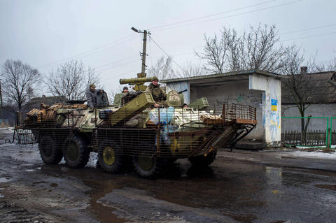 Ukrainian servicemen ride an APC at the frontline in the village of Orlovka, near the city of Donetsk, on Jan. 23, 2015.