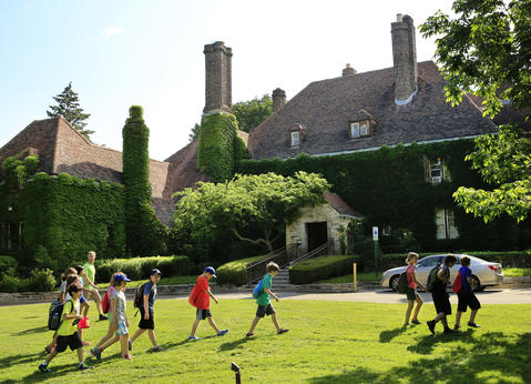 Day-campers on their way to the beach pass by the Harley Clarke Mansion's west-facing front in Evanston on July 10, 2013.