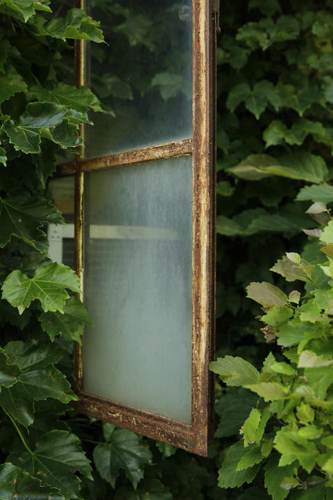 A window with a rusting frame at the Harley Clarke Mansion in Evanston.