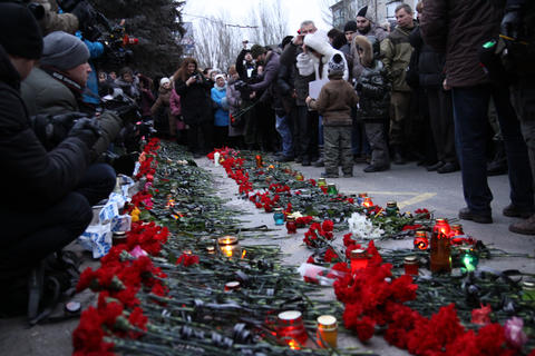 People lay flowers and set candles on Jan. 24, 2015, during a rally at a bus stop in Donetsk, eastern Ukraine, where 13 people were killed in a trolleybus shelling on January 22.