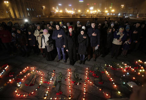 "People sing the Ukrainian national anthem next to candles set to form the word ""Mariupol"" on Independence Square in Kiev on Jan. 24, 2015 in memory of people who died during shelling."