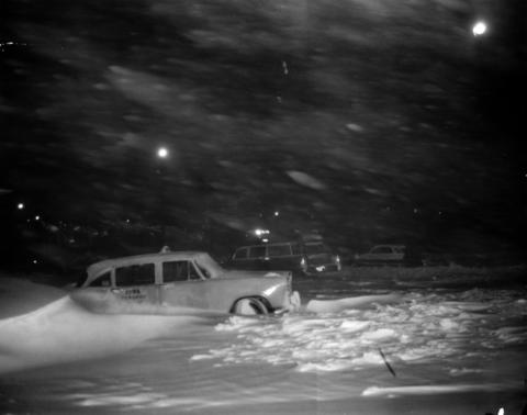 A taxi took on a desolate look as night fell and the drifts piled up during the January 1967 blizzard.