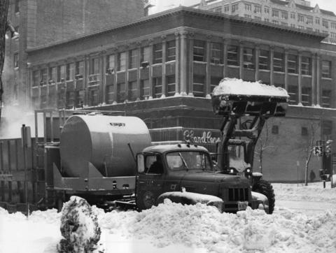A city thermal snow melter and a front-end loader team up against snow accumulation at Michigan Avenue and Erie Street on Jan. 27, 1967. The super-heated melter quickly reduces the snow.
