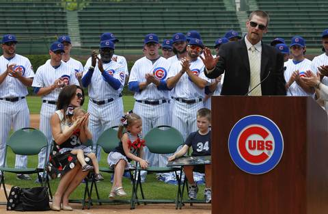 With his Cubs teammates behind him, Kerry Wood formally announces his retirement. Sitting are his wife Sarah with daughters Charlie and Katie and his son Justin.