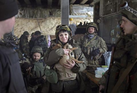 A female Ukrainian serviceman holds a dog at the checkpoint under the bridge of Peski village near of Donetsk, Ukraine