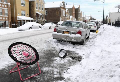 A dash of color is provided by a child's chair to mark a parking spot cleared of snow in Pilsen.