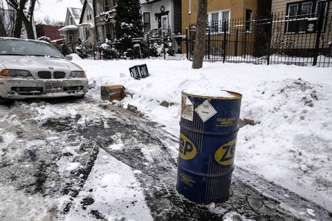 "A spot cleared of snow is claimed with a metal barrel marked ""poison,"" on North Sawyer Avenue in Chicago."