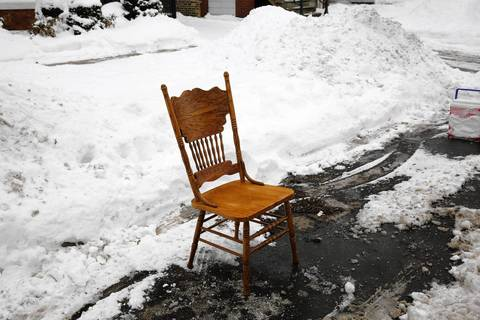 A wooden chair marks a parking spot on Ridgeway Avenue near School Street in Chicago.