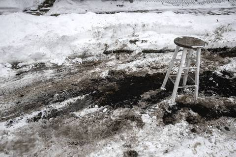 A stool is placed to save a parking spot a resident cleared of snow on McLean Avenue at Kedzie Avenue in Chicago.