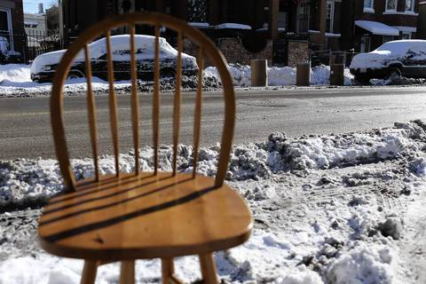 A wooden chair marks one cleared parking spot as three large barrels save another spot on the opposite side of the street on South Central Park Avenue in Chicago.