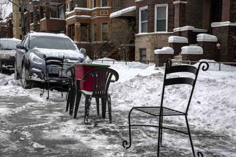 Patio chairs and a storage container save a spot on Walton Street at Washtenaw Avenue.