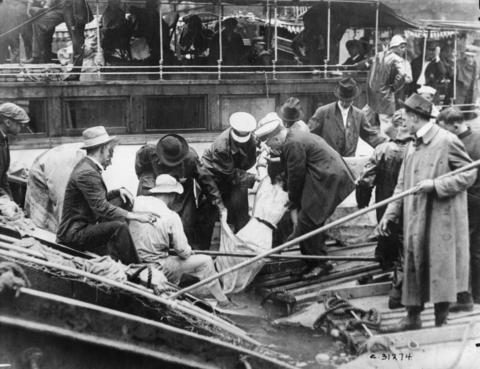 Rescuers recover the body of a girl from the Chicago River, a victim of the Eastland disaster on July 24, 1915.