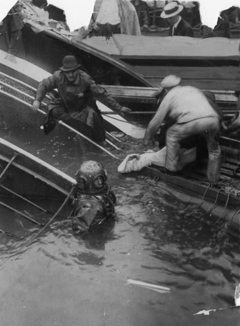 Rescuers lift the body of a woman from the wrecked SS Eastland while a diver who retrieved her prepares to return to find more victims. Divers equipped with metal-cutting torches were needed to break through the sides of the Eastland.
