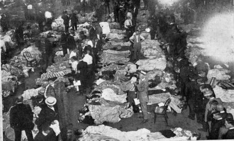 "Victims of the Eastland disaster were laid out in temporary morgues in buildings along the Chicago River. ""Grewsome scene in temporary morgue, Second Regiment Armory, where over 700 bodies were removed to, immediately after being recovered,"" is written on the back of this photograph."