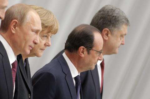 Russian President Vladimir Putin, German Chancellor Angela Merkel, French President Francois Hollande and Ukrainian President Petro Poroshenko pose during for a group photo during the Ukraine peace talks, Feb. 11 2015.