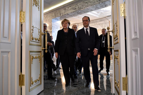 German Chancellor Angela Merkel and French President Francois Hollande arrive for a briefing in Minsk on Feb. 12, 2015.