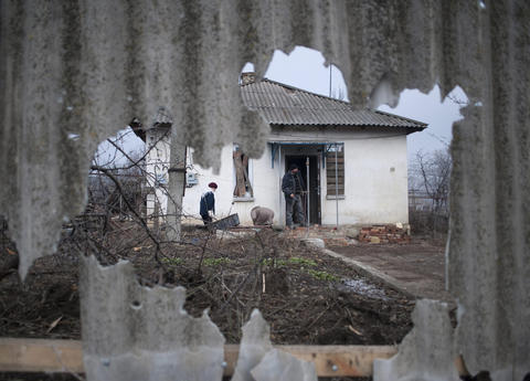 Villagers are seen Feb. 15, 2015, through a damaged fence after shelling the day before in Opytne, not far from the Donetsk area of Ukraine.