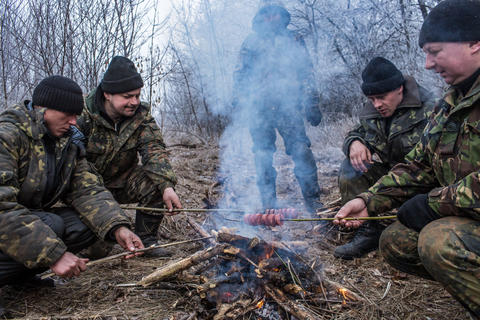 Ukrainian soldiers cook sausages over a fire Feb. 15, 2015, along the road leading to the embattled town of Debaltseve, Ukraine.