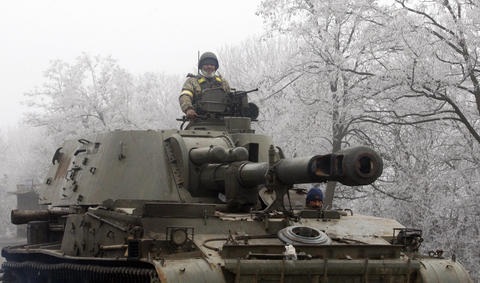 Ukrainian service members patrol with an artillery gun on the road between Artemivsk and Debaltseve in the Donetsk region of Ukraine on Feb. 15, 2015.