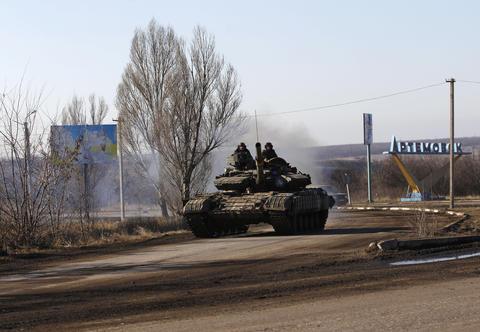Ukrainian government troops ride a tank toward Debaltseve near the town of Artemivsk, Ukraine, on Feb. 13, 2015.