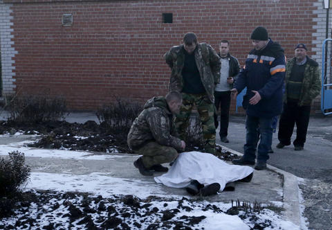 Ukrainian soldiers inspect the body of a child after shelling between Russia-backed separatists and Ukrainian government forces Feb. 13, 2015, in Artemivsk, Ukraine.