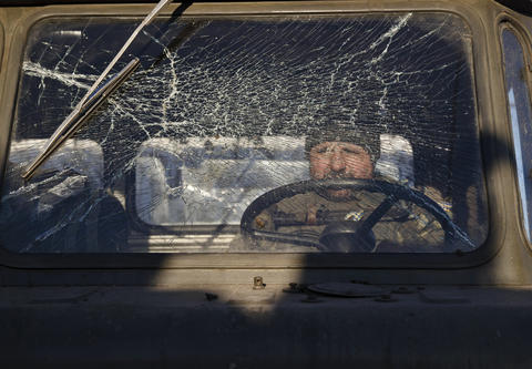 A Ukrainian serviceman sits inside a broken-down vehicle while pulling out of Debaltseve on Feb. 18, 2015.
