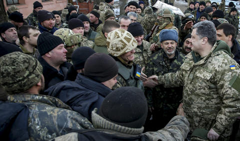 Ukrainian President Petro Poroshenko, right, speaks with servicemen Feb. 18, 2015, during a visit to the eastern city of Artemivsk.