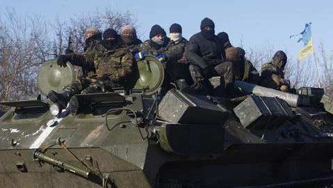 Ukrainian servicemen ride on top of an armored personnel carrier on the way from Artemivsk to Debaltseve on Feb. 17, 2015.