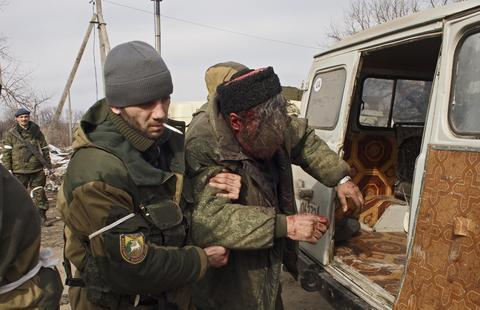 A wounded Cossack is carried away by fellow fighters after his car hit a land mine in the east Ukraine town of Debaltseve.