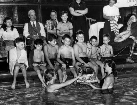 Instructors Ann Hutchinson, left, and Rose Johnson, right, both in water, serve candy canes at a yule party for post-polio patients in Glencoe, Ill., on Dec. 22, 1953. Sitting on the edge of the pool are, from left, Michael Pocin, Don Riederer, Larry Walls, John Thomson, Wayne Belec, John Marshall, and Robert O'Brien. Hutchinson and Johnson are both volunteer swim instructors.