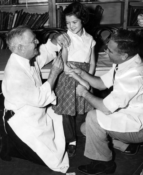 Board of Health president Dr. Herman Bundesen, left, gives the first polio shot at Mulligan Elementary School in Lincoln Park to Susan Lehman, 7, on Nov. 9, 1955. Dr. Morton Andelman assists on the right.