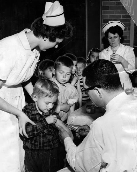 Dr. Burton J. Winston, right, the city physician, administers the polio vaccine to 1,059 children from Waukegan and surrounding schools at St. Theresa's Nursing home on April 18, 1955.
