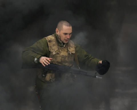 A recently mobilized Ukrainian serviceman balances on a smoke-engulfed beam during military training outside of Kiev, Ukraine, on Feb. 13, 2015.