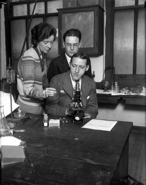 "Research assistant Ruth McKinney, from left, Dr. R. Wendell Harrison and Dr. Isidore S. Falk (seated), in December 1929. Falk, 30, of the University of Chicago, isolated the pleomorphic streptococcus, commonly known as the influenza germ, on Dec. 12, 1929. Falk was a professor of hygiene and bacteriology at the university. During the 1928 flu epidemic, 14 members of the bacteriology department became ill, including McKinney, many of them working 16-hour days and sleeping on their desks, according to Tribune reports. McKinney provided the flu virus that was finally isolated. In 1929 he cautiously stated that there is a ""hopeful prospect"" that an antitoxin for influenza would now be discovered."