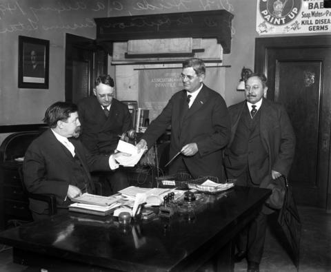 Dr. John Dill Robertson, left, with D. H. Heide, C. A. Alling and Lucius Tetar in Robertson's office. Robertson was Chicago's health commissioner during the 1918 influenza pandemic that killed thousands of Chicagoans. On the back wall is the 1916 organizational chart for the newly formed Association for the Prevention of Infantile Paralysis (polio). Undated photo.