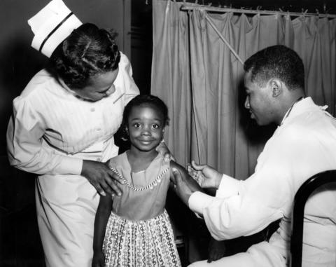 Patricia Ann Green, 5, gets a polio vaccine shot from Dr. Fritz LaRoche, of Provident Hospital, at Lamson Auditorium at 5034 S. Vincennes Ave. in Chicago in July 1956. Comforting Green is director of nursing Beatrice A. Norris.