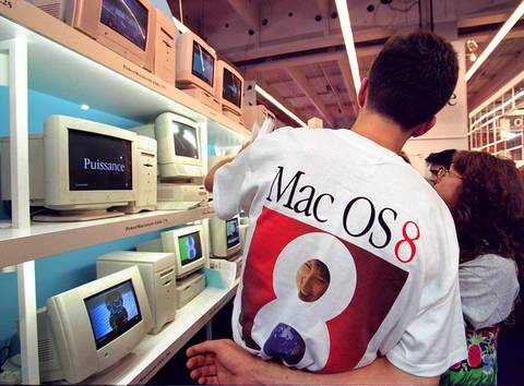 An Apple employee shows new models during the Apple Expo at the Porte de Versailles exhibition in Paris on Sept. 18, 1997.