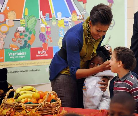 Michelle Obama hugs students during a break from passing out fresh fruit to students at Hollin Meadows Elementary School in Alexandria, Va. Obama was promoting the Healthier U.S. Schools Challenge which focuses on three core principles: nutritious meals, nutrition education, and physical education.