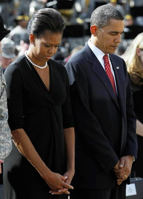 Michelle Obama and President Barack Obama bow their heads in prayer at the start of the III Corps and Fort Hood Memorial Ceremony held to honor the 13 victims of the shootings on the Fort Hood Army post in Fort Hood, Texas.