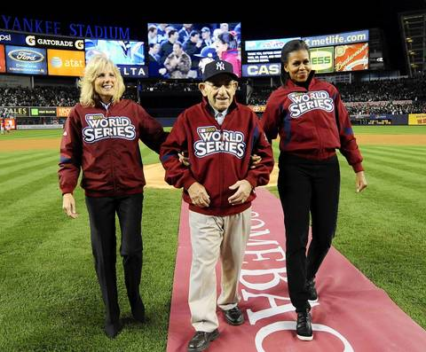 Jill Biden, left, and Michelle Obama accompany Yogi Berra on the field during ceremonies before Game 1 of the 2009 World Series between the Philadelphia Phillies and the New York Yankees at Yankee Stadium.