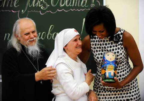 Michelle Obama hugs an elderly nurse while holding a traditional Russian matreshka nesting doll during a visit to the Sisters of Mercy St. Dmitry Nursing College in Moscow.