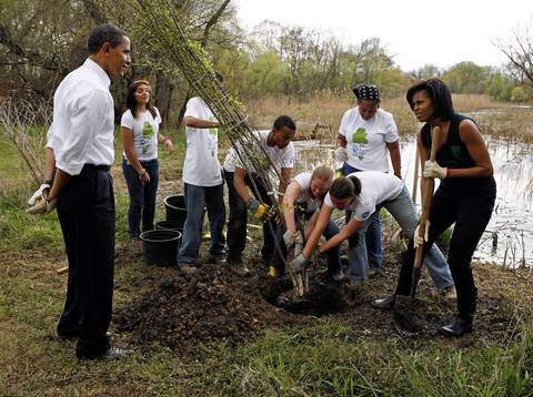 Michelle Obama and and President Barack Obama participate in a tree planting event at the Kenilworth Aquatic Gardens in Washington, DC. The event was organized by the Student Conservation Association, an Americorp organization.