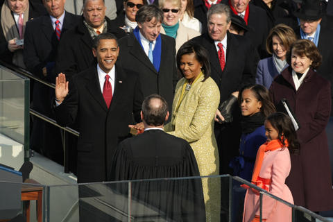 Barack Obama, with wife Michelle and daughters Malia and Sasha at his side, takes the oath of office administered by Chief Justice John Roberts.