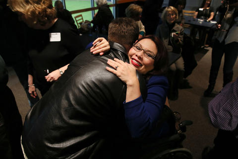 U.S. Rep. Tammy Duckworth gives her former helicopter crew chief, Philip Haffron, a hug after delivering her election victory speech at Boomers Stadium in Schaumburg on Nov. 4, 2014.