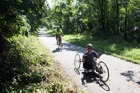 Tammy Duckworth, trains on her hand-cranked racing chair on the Capital Crescent Trail in Washington D.C. on Aug. 23, 2009. Her husband, Bryan Bowlsbey bikes behind her.
