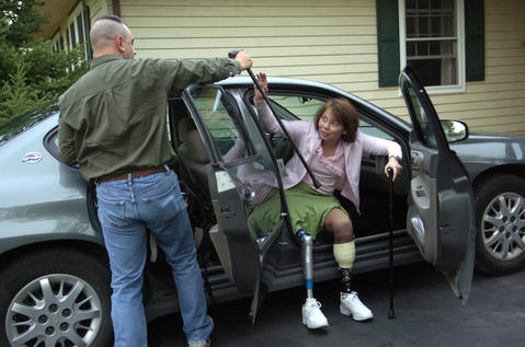 Army National Guard Captain Tammy Duckworth takes her walking canes from her husband Bryan Bowlsbey as she arrives home in Hoffman Estates on June 3, 2005. Duckworth and her helicopter crew were shot down in Iraq. She lost both of her legs.