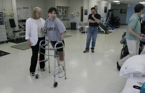 Physical therapist Bunnie Nychoff helps Army National Guard Major Tammy Duckworth walk with a new prosthetic right leg as her husband Brian Bowslbey watches how it fits at Walter Reed Army Medical Center in Washington on April 28, 2005.
