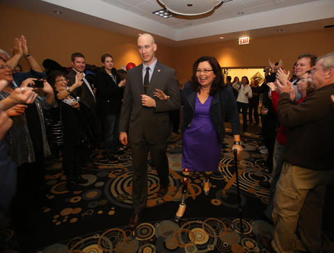 8th Congressional District candidate Tammy Duckworth, escorted by friend Scott Waddle, enters a ballroom, after defeating freshman Republican Rep. Joe Walsh, to give her victory speech in Elk Grove Village, Ill., on Nov. 6, 2012.