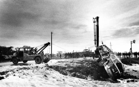 Dec. 17, 1977: A Schaumburg fire truck is slowly lifted upright near Higgins and Meacham roads. Schaumburg firefighter Anthony Gallo was killed when the truck swerved to avoid a car, hit a patch of ice and rolled into a ditch.